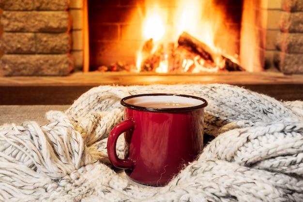 Gemütliche szene in der nähe des kamins mit einem rot emaillierten becher mit heißem tee und einem gemütlichen warmen schal.