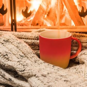 Gemütliche szene in der nähe des kamins mit einer roten tasse heißen tee und einem gemütlichen warmen schal.