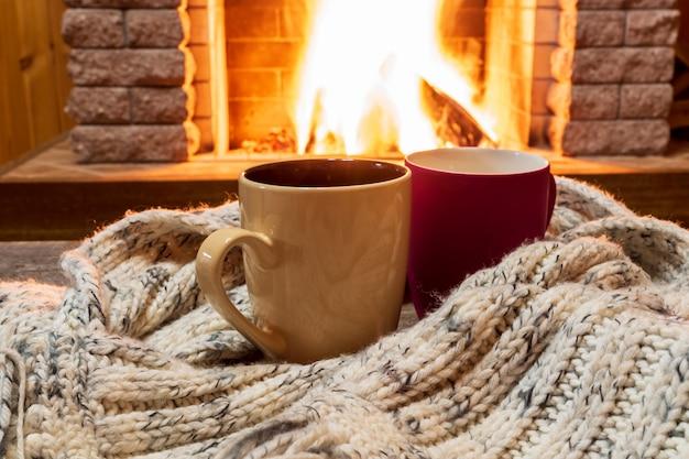 Gemütliche szene in der nähe von kamin mit tassen heißem tee und einem gemütlichen warmen schal.