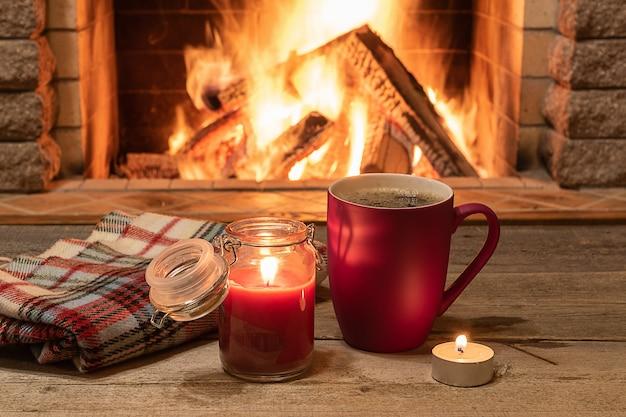 Gemütliche szene nahe kamin mit becher heißem tee, warmem schal und kerze.