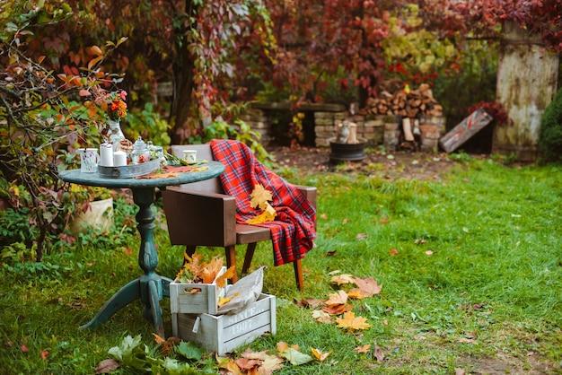 Gemütliche terrasse. herbstblätter liegen auf einem antiken runden holztisch mit geschirrbechern, keksen und kerzen. neben einem alten stuhl mit buntem teppich und holzkisten auf dem boden. herbst hinterhof dunkel