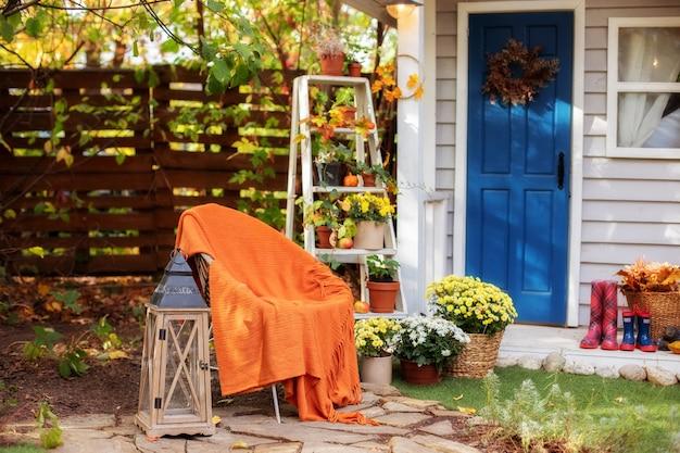 Gemütliche terrasse mit stuhl, plaid, holzlaterne, topfchrysanthemen. stilvolles herbstdekor auf der veranda nach hause zum entspannen