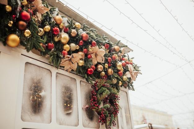Gemütliche weihnachtsdekoration. rote und goldene kugeln und weihnachtskranz an ladenfront oder gebäudefassade. weihnachtsfest festliches straßendekor, feiertagswintermesse.