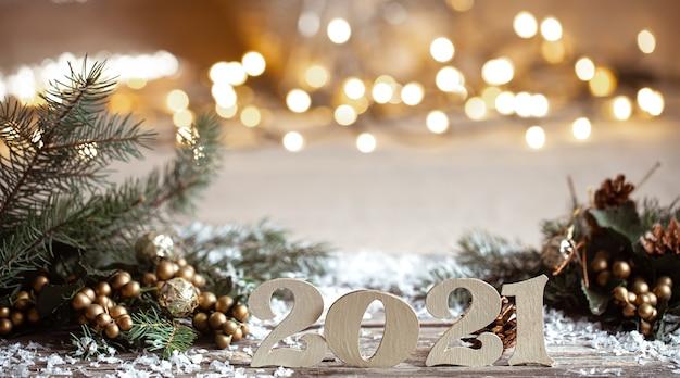 Gemütliche weihnachtsdekorationsnummern aus holz 2021 auf verschwommenen lichtern.