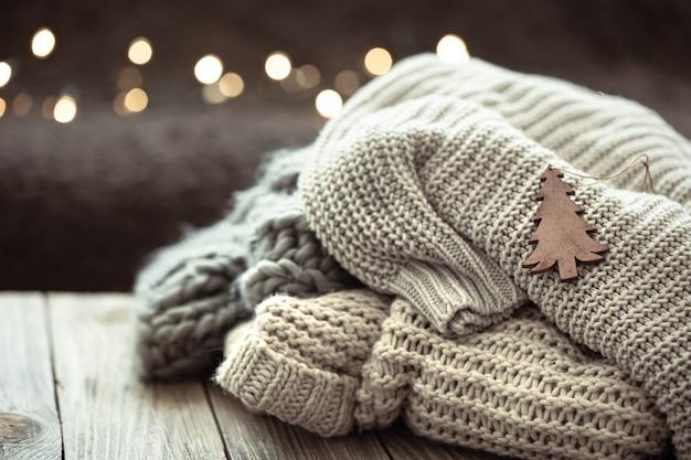 Gemütliche weihnachtskomposition mit einem stapel gestrickter pullover auf verschwommenem hintergrund mit bokeh.