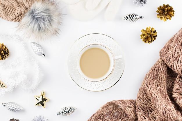 Gemütliche winterkleidung, heißes getränk und weihnachtsdekorationsrahmen
