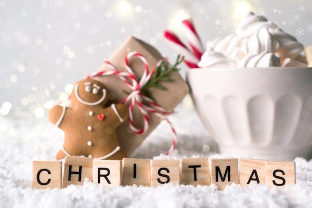 Gemütliche winterkomposition mit einer tasse heißer schokolade mit marshmallows-lebkuchenmannplätzchen und geschenk auf einem leichten fest. weihnachtswort aus briefen