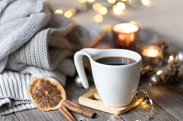 Gemütliche winterkomposition mit einer tasse tee auf verschwommenem hintergrund mit brennenden kerzen und bokeh-lichtern und gestrickten elementen.