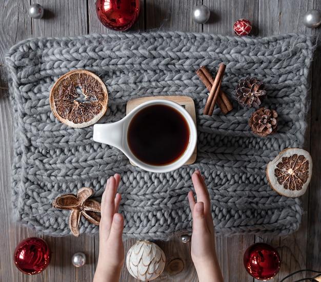 Gemütliche wohnkomposition mit einer tasse tee, kinderhänden, gestricktem element, weihnachtsdekordetails, flacher lage.