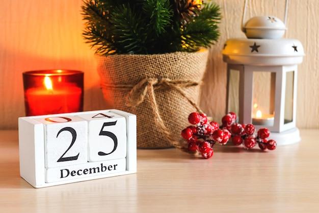 Gemütliche wohnkultur komposition mit kerzen laterne weihnachtsbaum und kalenderdatum 25. dezember