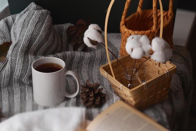 Gemütliche wohnkultur mit warmer atmosphäre. weiße tasse mit heißem tee und gestrickter kleidung