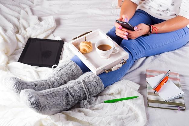 Gemütlicher abend, warme wollsocken, weiche decke, kerzen. frau, die sich zu hause, trinkender kakao, unter verwendung des laptops entspannt. bequemer lebensstil.