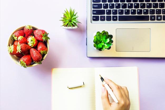 Gemütlicher arbeitsplatz des frühlings mit einem laptop, einem notizbuch, einer schüssel erdbeeren