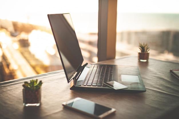 Gemütlicher arbeitsplatz im innenministerium mit laptop auf tabelle gegen die fenster bei sonnenuntergang für das on-line-geschäft, arbeitend, studieren. heimarbeit