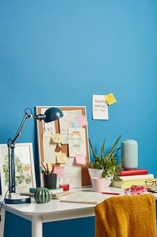 Gemütlicher arbeitsplatz mit notizbüchern, getränken, schreibtischlampe und verschiedenen notizen an der wand in der nähe. erinnern sie daran, was zu tun ist, und schreiben sie tägliche aufgaben. studenten desktop mit den notwendigen materialien.
