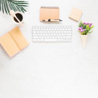 Gemütlicher arbeitsplatz mit tastatur und notizbuch