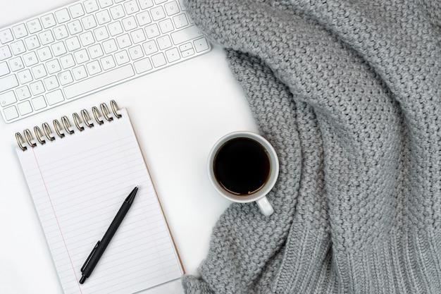 Gemütlicher arbeitsplatz mit warmem pulloverkaffee, notizblock