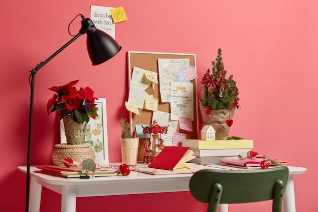 Gemütlicher arbeitsplatz ohne menschen. weißer schreibtisch mit notizblöcken, lampe, kleine verzierte weihnachtstanne, die kommenden feiertag symbolisiert
