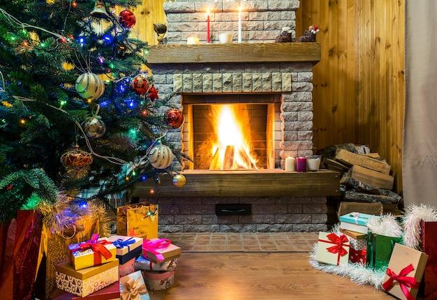 Gemütlicher brennender kamin. weihnachtsbaum verzierte spielwaren und weihnachtslichter, geschenkboxen und kerzen auf boden.