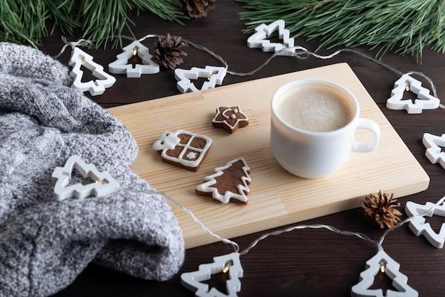 Gemütlicher feiertagstisch mit einer tasse kaffee und weihnachtsplätzchen. winterabend.