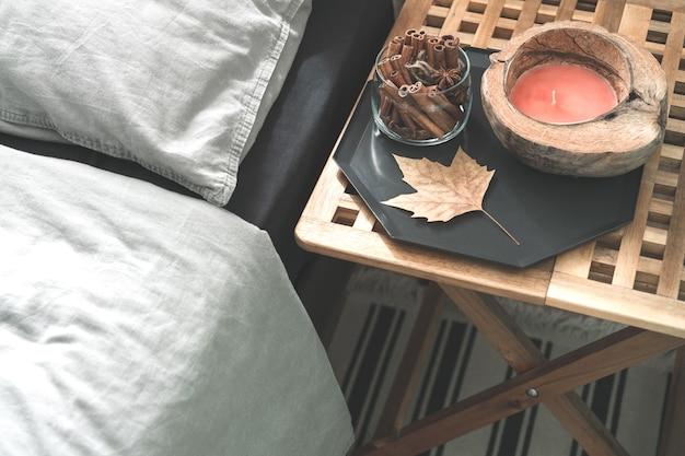 Gemütlicher grauer schlafzimmerinnenraum mit bequemem bett nahe hölzernem nachttisch mit kerze