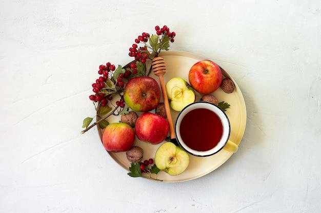 Gemütlicher herbstlicher gewürztee mit honig, äpfeln und roten weißdornbeeren auf einem tablett. stillleben auf weißem hintergrund. flach liegen.