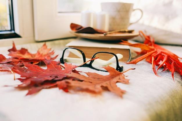Gemütlicher herbstmorgen mit tasse kaffee mit sahne und herbstlaub herbst- und feiertagskonzept. draufsicht der flachen lage