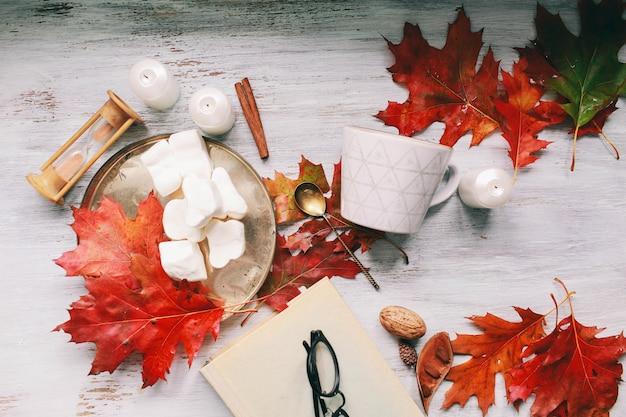 Gemütlicher herbstmorgen mit tasse kaffee mit sahne und herbstlaub herbst- und feiertagskonzept.