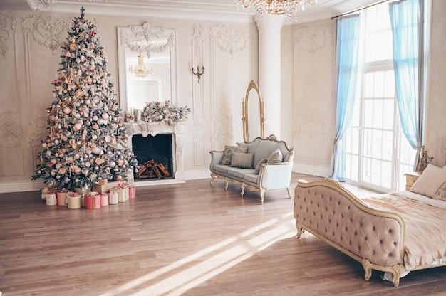 Gemütlicher innenraum des klassischen weißen schlafzimmers mit weihnachtsbaumdekorationen.