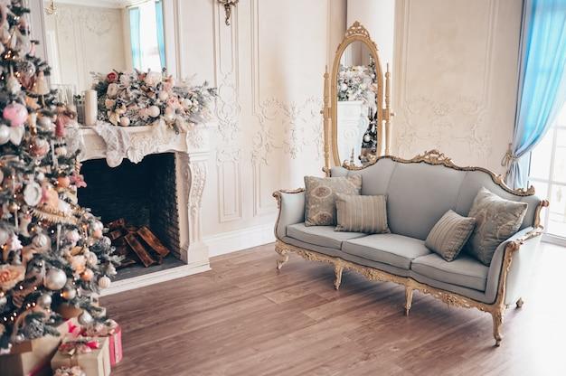 Gemütlicher innenraum des klassischen weißen wohnzimmers mit weihnachtsdekorationen.