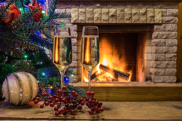 Gemütlicher kamin. champagne-wein vor weihnachtsbaum verzierte spielwaren und weihnachtslichter im berghäuschen.
