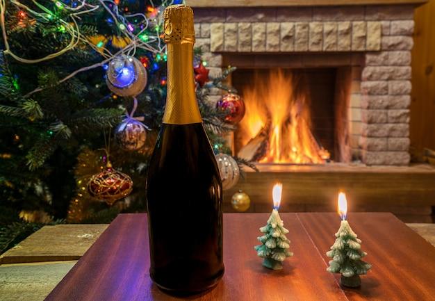 Gemütlicher kamin. champagnerwein und kerzen vor weihnachtsbaum verzierten spielwaren und weihnachtslichter.