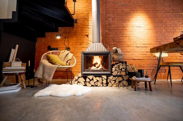 Gemütlicher kamin mit brennholz im loft-stil mit backsteinmauerhintergrund, brennendem feuer im kamin, hausbehaglichkeit im winter