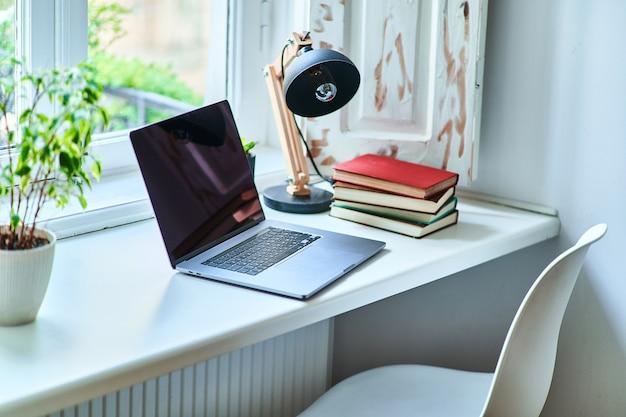 Gemütlicher, komfortabler, gemütlicher arbeitsplatz am fenster in einem weißen innenraum