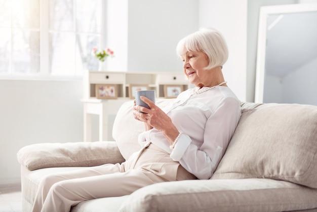 Gemütlicher morgen. charmante ältere frau, die auf der bequemen couch sitzt, eine tasse kaffee hält und geistesabwesend ansieht, tief in gedanken versunken