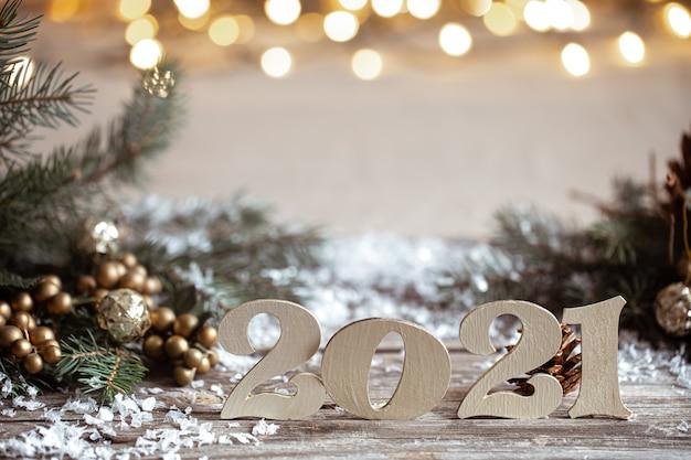 Gemütlicher weihnachtshintergrund mit dekorativen hölzernen 2021 zahlen auf unscharfem hintergrund mit lichtern.