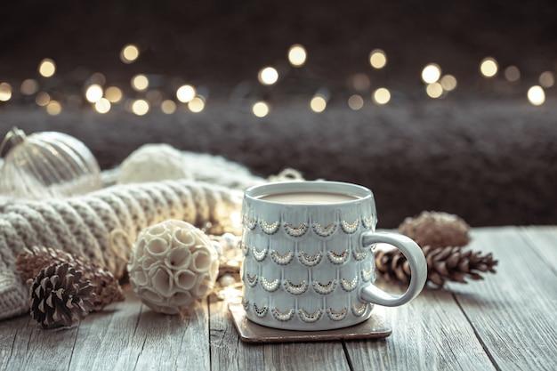 Gemütlicher weihnachtshintergrund mit einer schönen tasse und dekordetails auf einem unscharfen hintergrund mit bokeh.