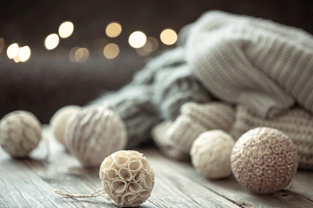 Gemütlicher weihnachtshintergrund mit weihnachtsschmuck und gestricktem element auf unscharfem hintergrund.