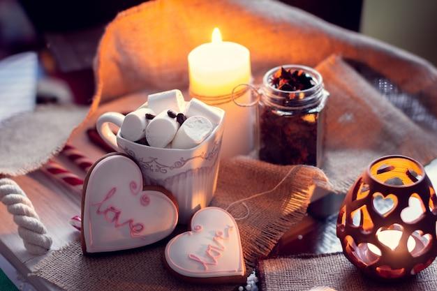 Gemütlicher winter bei kerzen und tasse kaffee mit marshmallow- und ingwerschnaps