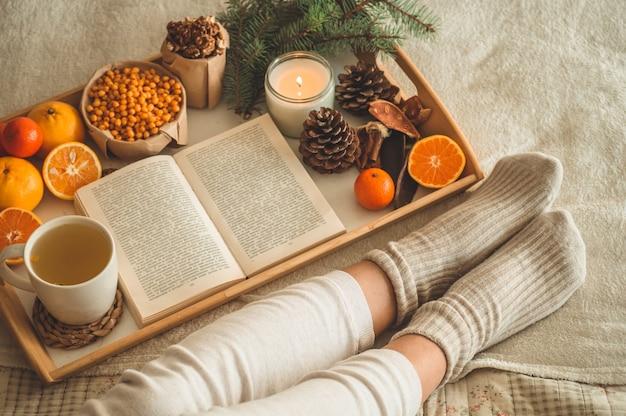 Gemütlicher winterabend, warme wollsocken. frau liegt füße hoch auf weißer zotteliger decke und lesebuch. gemütliche freizeitszene. text im buch ist nicht lesbar. frau, die zu hause entspannt. bequemer lebensstil.