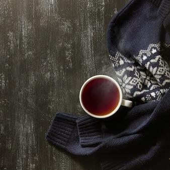 Gemütlicher winterhaushintergrund, tasse heißer tee und warmer gestrickter pullover auf schwarzem tisch.