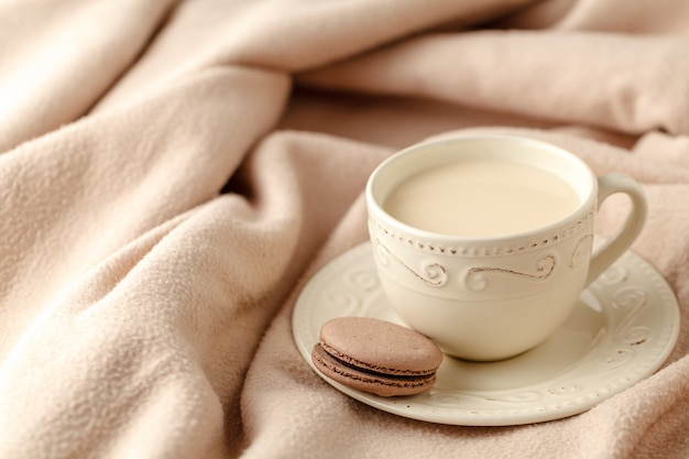 Gemütlicher winterheimhintergrund, tasse heißen kaffees mit milch, warmer gestrickter pullover auf weißem betthintergrund, weinlese-ton. lifestyle-konzept
