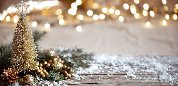 Gemütlicher winterhintergrund mit festlichen dekordetails, schnee auf einem holztisch und bokeh. konzept einer festlichen atmosphäre zu hause.