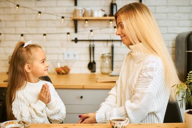 Gemütliches bild des verblüfften entzückenden kleinen mädchens mit aufgeregtem blick, der am küchentisch mit ihrer mutter kocht oder frühstückt, tee trinkt, warme pullover trägt. gemütliche festliche atmosphäre