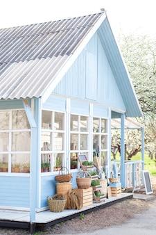 Gemütliches blaues haus mit einem schönen garten an einem sonnigen tag. rustikaler stil. herbstkonzept. haus auf dem land. englisches landhaus. schönes bauernhaus mit weidenkörben mit ernte.