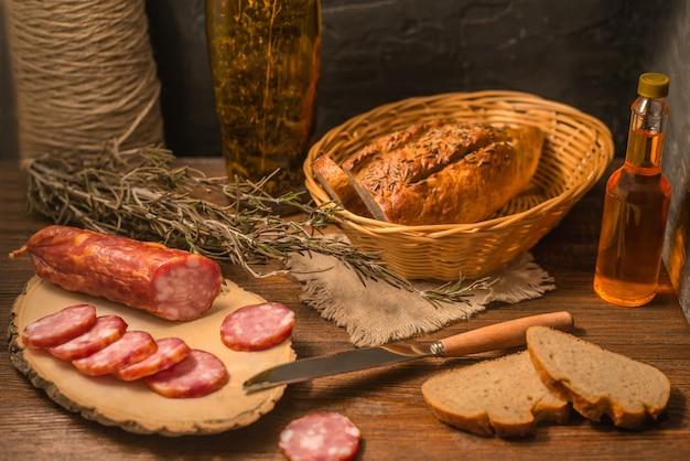 Gemütliches essensstillleben mit wurst, rosmarin und brot