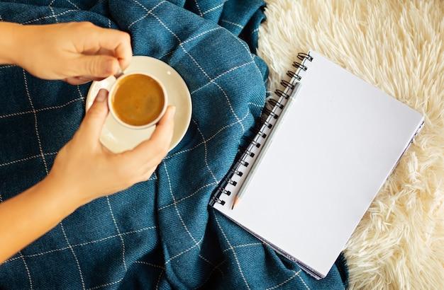 Gemütliches flatlay mit holztablett, hände halten tasse kaffee, kerze, notizbuch auf weißen, flauschigen laken und blauer decke. konzept zu hause arbeiten. ansicht von oben.