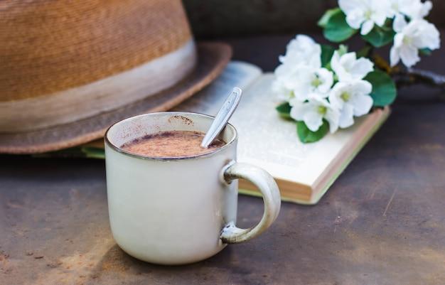 Gemütliches frühlingsstillleben auf dunklem hintergrund. eine tasse kaffee, ein buch, ein blühender apfelbaumzweig und ein hut. foto im vintage-stil, blumenarrangement mit zweig