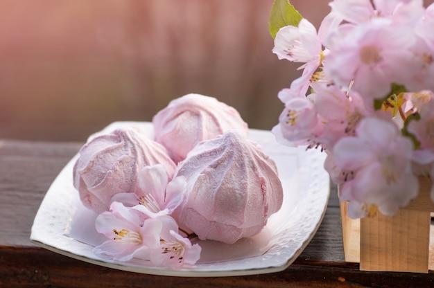 Gemütliches frühlingsstillleben: tasse heißen tee mit frühlingsblumenstrauß auf vintage-fensterbank mit einem rosa marshmallow. frühling. wohnung.