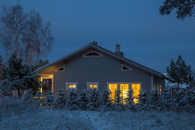 Gemütliches haus an einem winterabend mit leuchtenden fenstern. verschneiter vordereingang zum vorstadthaus. winter im garten